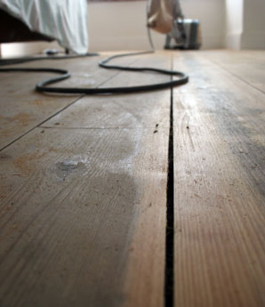 Aardvark floor sanding services in Norwich and Norfolk > image of stained wooden floor and sander